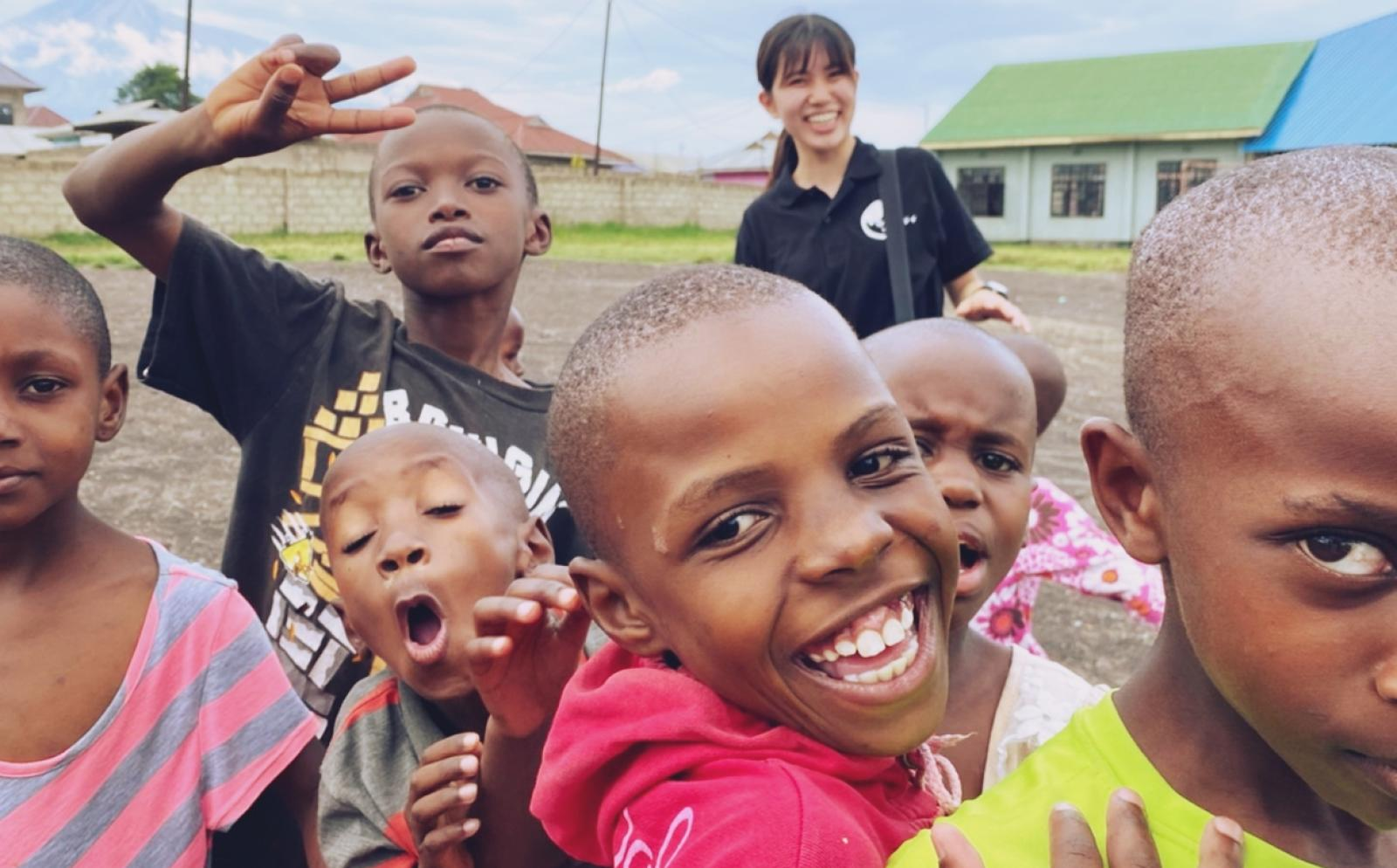 タンザニアでチャイルドケアボランティア中の鹿島友里花さんと元気いっぱいの現地の子供たちの写真